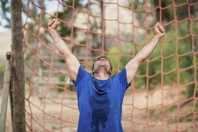 Happy man raising his hands during obstacle course