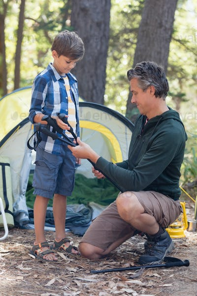 Father offering hiking poles to son in forest
