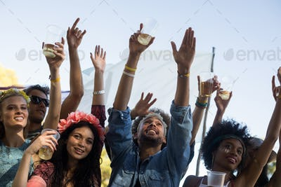 Friends holding beer glasses while enjoying music festival
