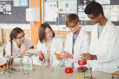 Attentive school kids doing a chemical experiment in laboratory