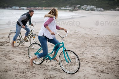 Mature couple riding bicycles on the beach