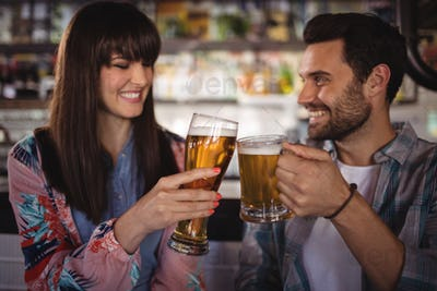 Happy couple toasting glasses of beer at counter