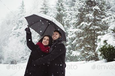 Smiling couple under umbrella pointing at view in forest