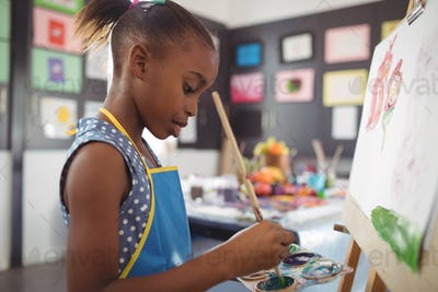 Side view of focused girl painting on canvas