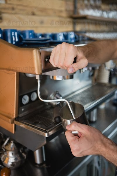 Close-up of waiter hands pouring milk in jug from coffee machine