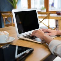 Cropped image of woman using laptop at table in careteria