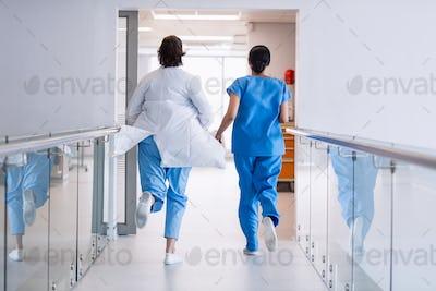 Nurse and doctor running in hospital corridor