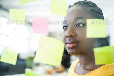 Female executive reading sticky notes