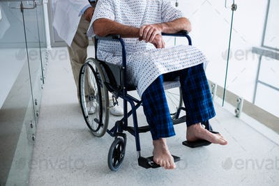 Doctor carrying a patient on a wheelchair