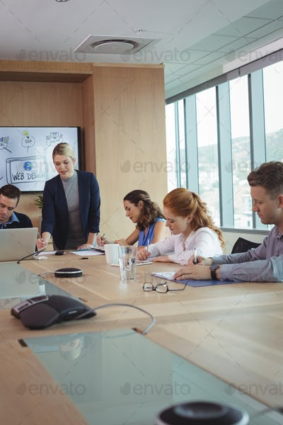 Young businesswoman with team working at conference table