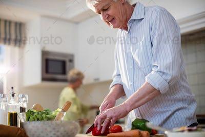 Senior man cutting vegetables for salad