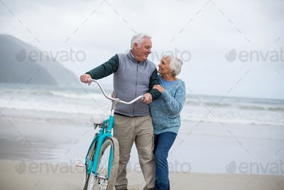 Senior couple standing with bicycle on the beach