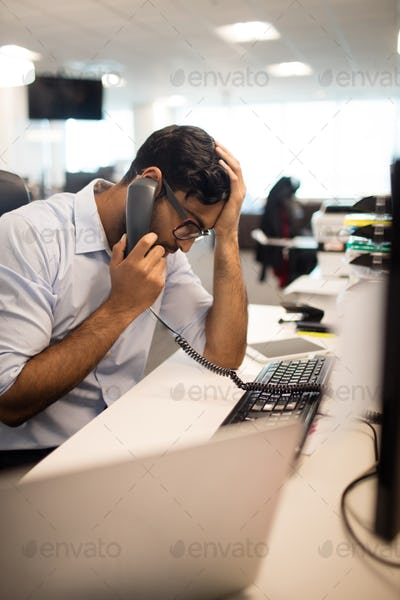 Tensed businessman talking on land line at desk
