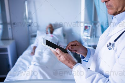 Mid-section of male doctor using digital tablet