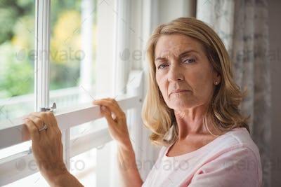 Portrait of senior woman standing next to window