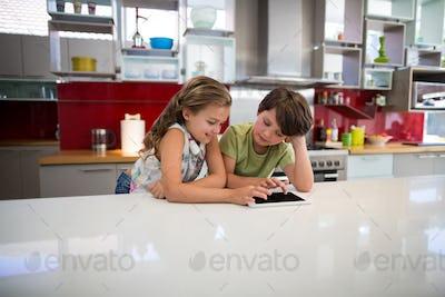 Happy siblings using digital tablet in kitchen