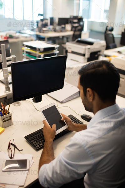 Businessman using digital tablet while sitting at his desk in office