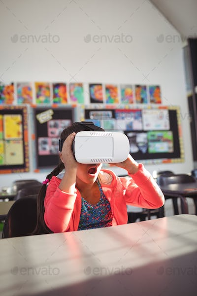 Surprised girl using virtual reality glasses in classroom
