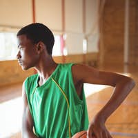 Teenage boy practicing in basketball court