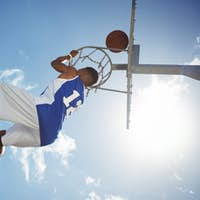 Low angle view of male teenager hanging on basketball hoop