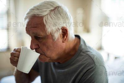 Worried senior man having black coffee in the bedroom