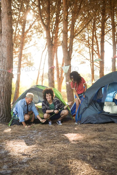 Happy man with friends setting up tent on field