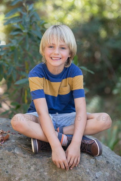 Smiling little boy sitting on rock in forest