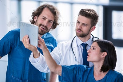 Surgeons and doctor looking at digital tablet
