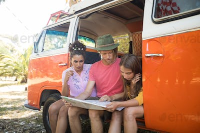 Friends reading map while sitting in camper van