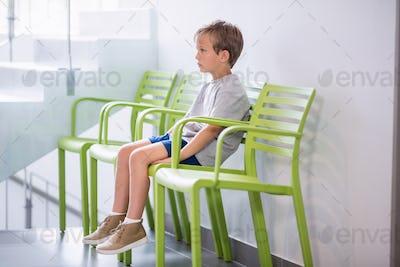 Upset boy sitting on chair in corridor