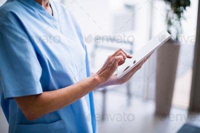 Nurse standing in hospital corridor using digital tablet