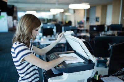 Businesswoman using copy machine in office