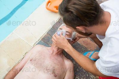 Lifeguard putting oxygen mask to senior man