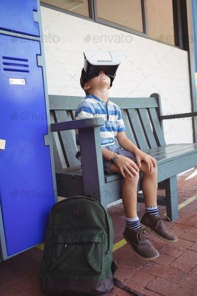 Boy using virtual reality glasses while sitting on bench