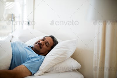Senior man sleeping in bedroom