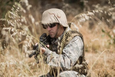 Military soldier hiding in grass while guarding with a rifle