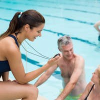 Young female trainer monitoring time of senior swimmers at poolside