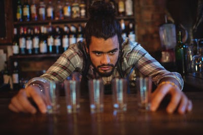 Waiter placing shot glasses on counter