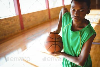 Portrait of teenage boy holding basketball
