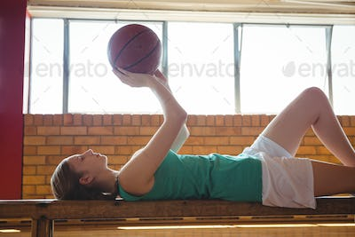Woman playing with basketball while lying on bench in court