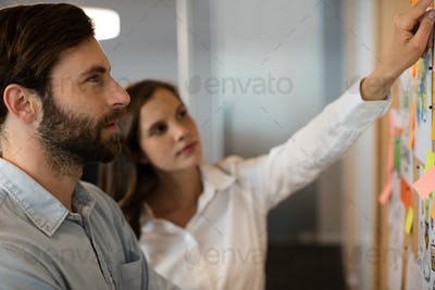Serious businessman analyzing charts with female colleague