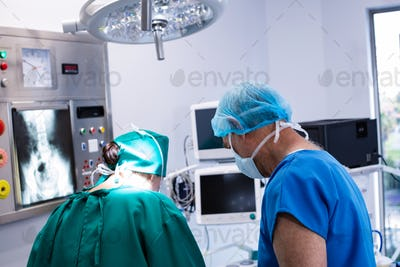 Male and female surgeon working in operation theater