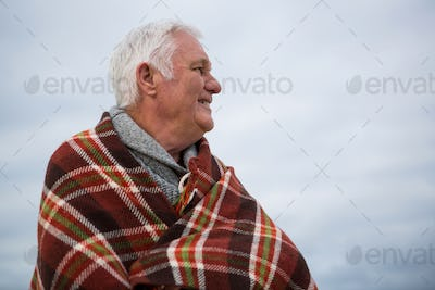Thoughtful senior man wrapped in shawl at the beach