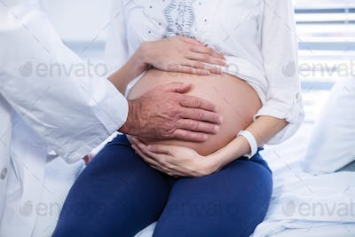 Mid section of doctor touching pregnant womans belly in ward