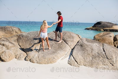 Couple holding hands while standing on rock at beach