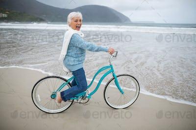 Senior woman riding bicycle on the beach