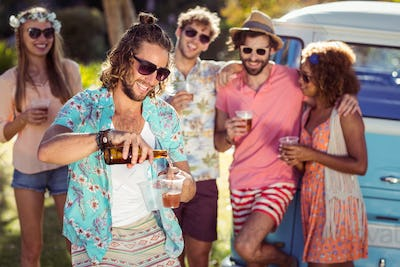 Happy man pouring beer in a glass while his friends standing in background