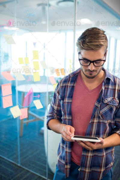 Man in office using digital tablet against sticky notes on wall