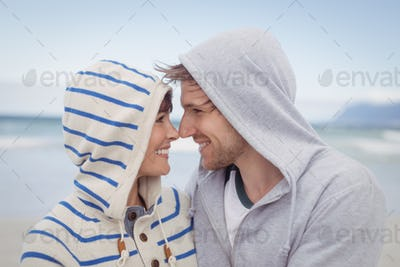 Smiling couple wearing hooded sweater during winter