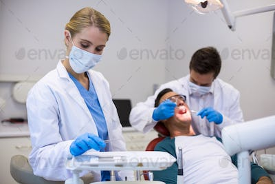 Dentist holding dental tool while his colleague examining patient in background